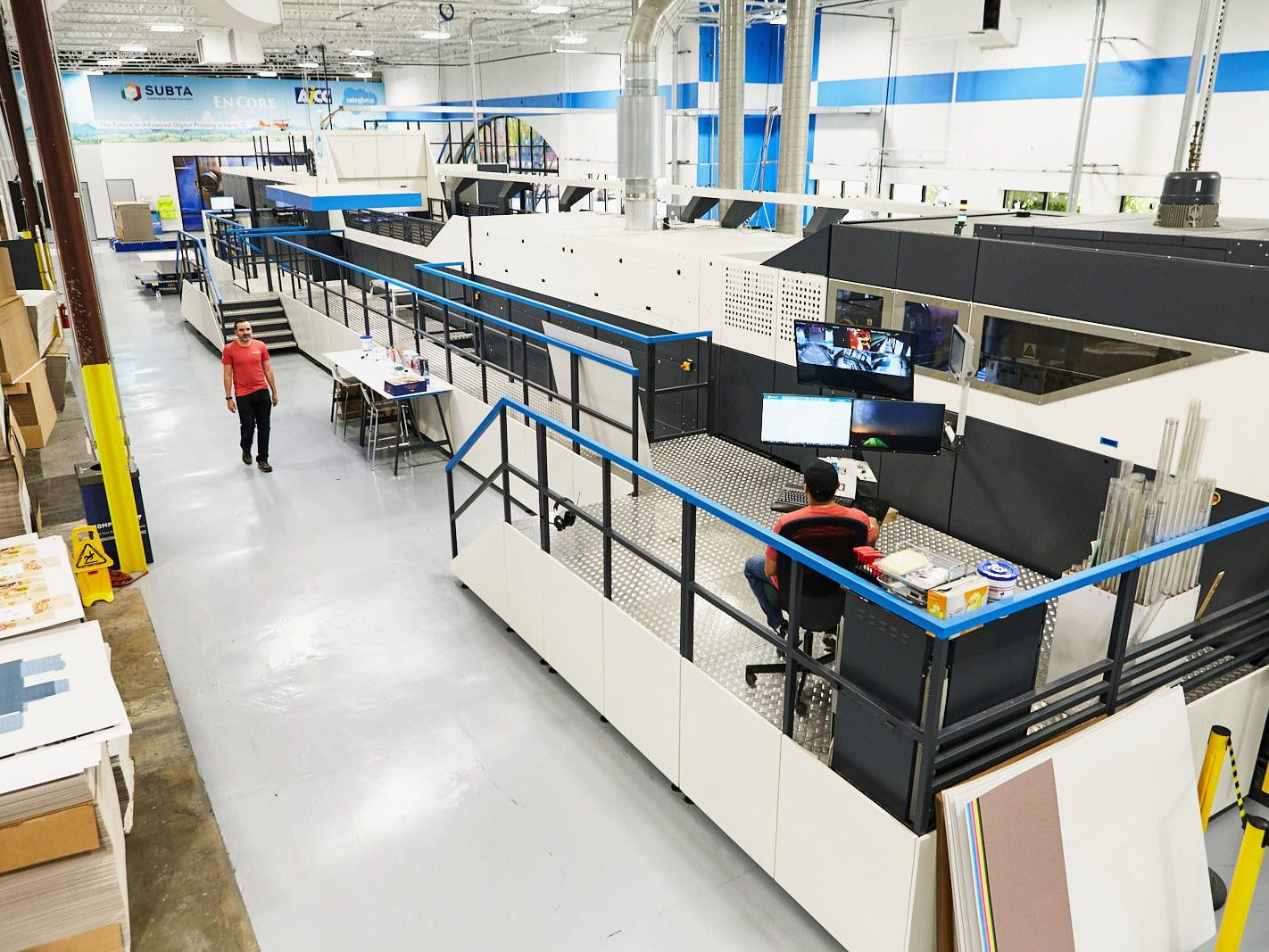 Two employees man a large industrial printer