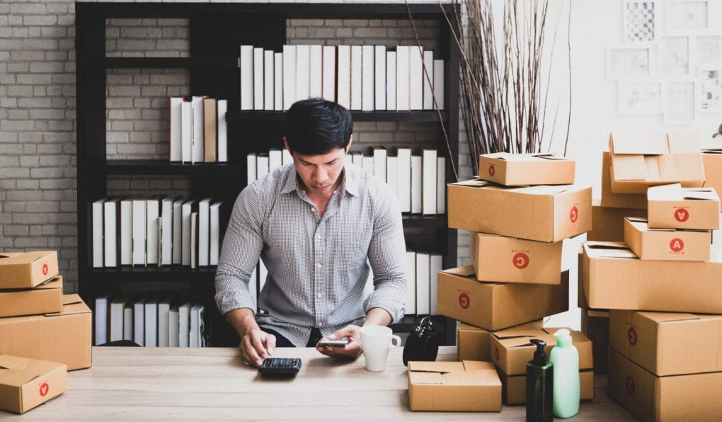 A man working in retail balances his books, sitting next to a pile of craft boxes.
