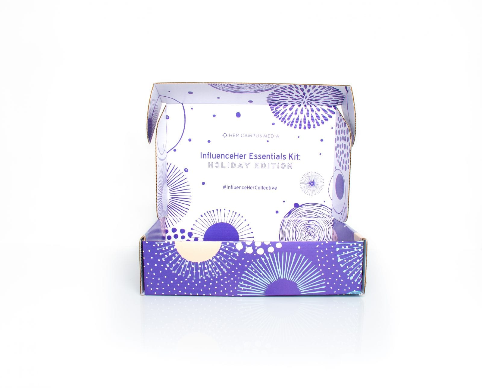 """colorful box that reads """"InfluenceHer Essestials Kit: Holiday Edition"""" on the inside flap"""