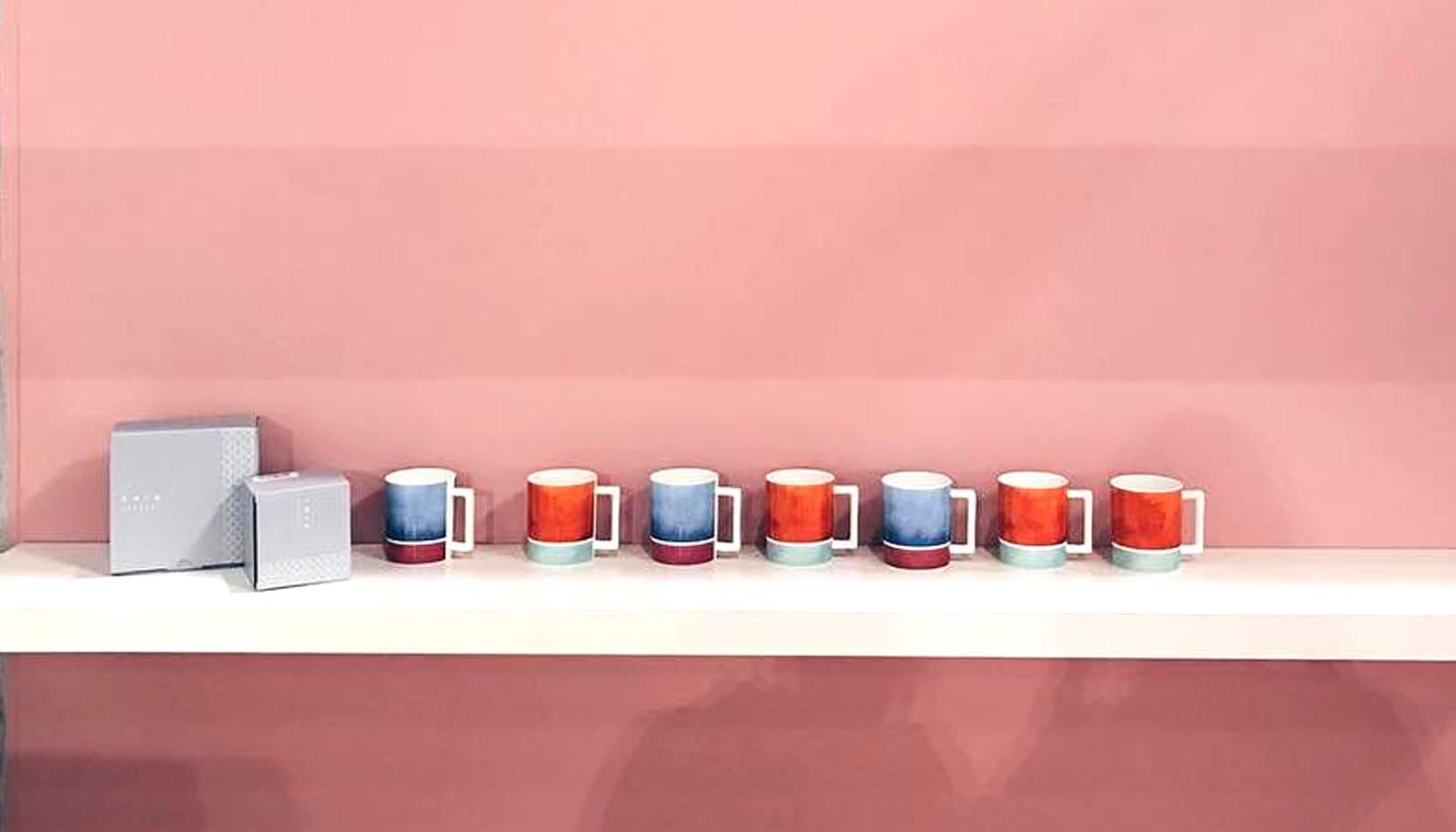 a row of mugs against a pink wall
