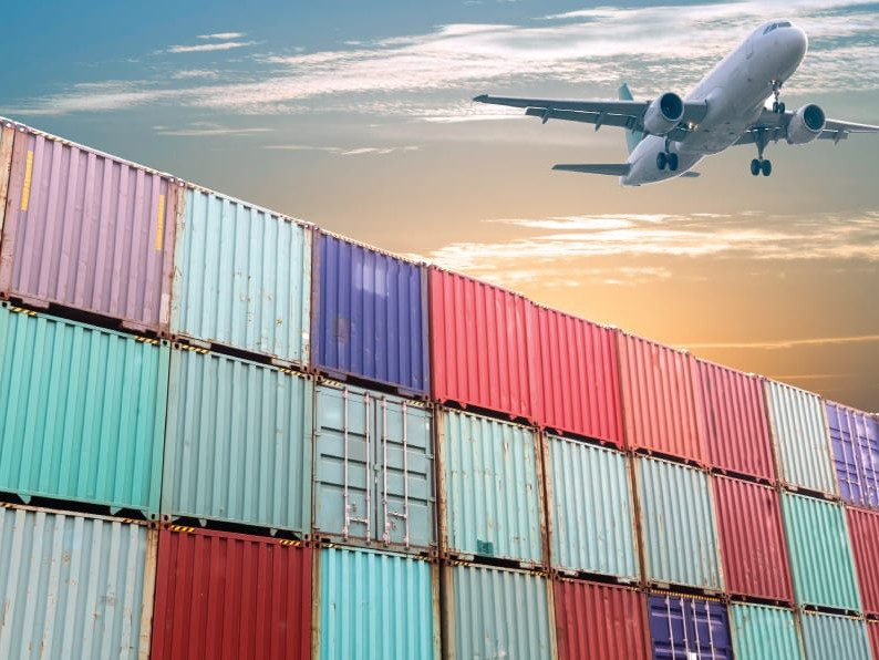 A plane flying over brightly colored shipping containers