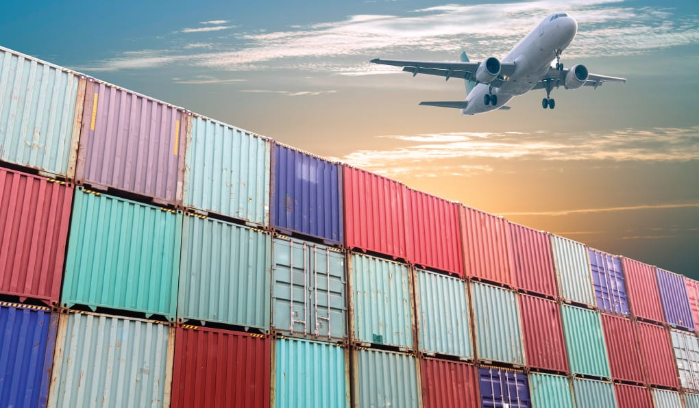 an airplane flying over a stack of shipping crates