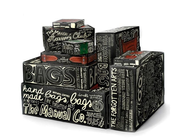 A selection of dark boxes with cream colored hand-drawn letters across all of them, covering each surface.