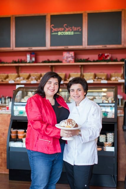 Photo of the owners of Seven Sisters Bakery in front of their display