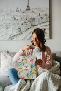 a young woman smiling as she opens a Bomibox and takes a picture of its contents